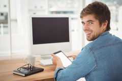 Happy businessman using digital tablet while sitting at desk. Portrait of happy businessman using digital tablet while sitting at desk in office Royalty Free Stock Images