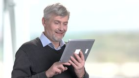Happy businessman using digital tablet standing in office. Mature businessman having funny conversation online using tablet. Bright blurred background stock video footage