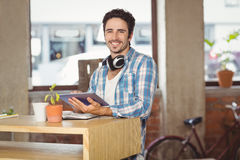 Happy businessman using digital tablet by table in office Royalty Free Stock Image