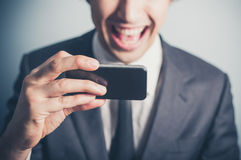 Happy businessman using his smartphone Royalty Free Stock Image