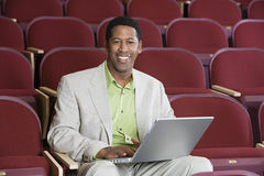 Happy Businessman Using Laptop In Auditorium Stock Photos
