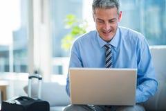 Happy businessman using laptop computer Stock Photo