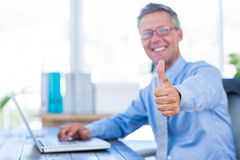 Happy businessman using laptop computer and looking at camera with thumbs up Stock Photo