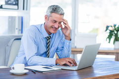 Happy businessman using laptop computer Royalty Free Stock Photography