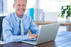 Happy businessman using laptop computer Stock Photos