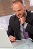 Happy businessman using laptop Stock Images