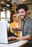 Happy businessman using laptop with female coworker Stock Photos