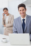 Happy businessman using a laptop before going to work Stock Images