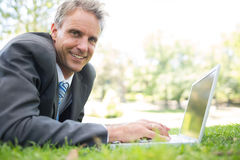 Happy businessman using laptop on grass. Portrait of happy businessman using laptop while lying on grass in park Stock Photos