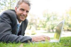 Happy businessman using laptop on grass Stock Photos
