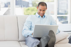 Happy businessman using laptop with his feet up Stock Photography