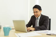 Happy businessman using laptop at his office desk.  Royalty Free Stock Images