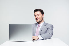 Happy businessman using laptop Stock Photography