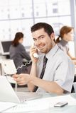 Happy businessman using laptop talking on phone. Happy businessman sitting at desk in office, talking on phone, using laptop, women working in the background Royalty Free Stock Photo