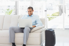 Happy businessman using laptop waiting to depart on business trip Stock Images