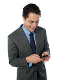 Happy businessman using a mobile phone Royalty Free Stock Photo