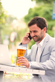 Happy businessman using mobile phone and laptop while holding beer glass at outdoor restaurant Stock Images