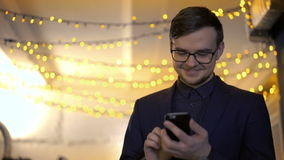 Happy businessman using phone on a background of a lights