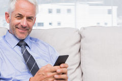Happy businessman using smartphone Royalty Free Stock Photography
