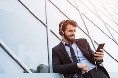 Happy businessman using smartphone with headphones near skyscraper windows. stock image
