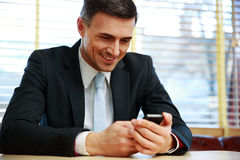 Happy businessman using smartphone Royalty Free Stock Photo