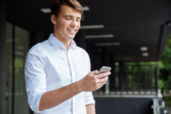 Happy businessman using smartphone and smiling near business center Stock Images