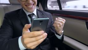 Happy businessman using smartphone and smiling, showing yes gesture in auto