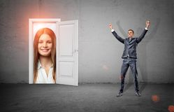 A happy businessman in victory motion stands in a room with a white door opening to a giant happy female face. stock image