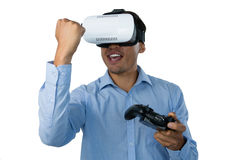 Happy businessman with vr glasses clenching fist while playing video game Royalty Free Stock Photography