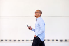 Happy businessman walking with cellphone Royalty Free Stock Photography