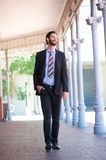 Happy businessman walking outside on sidewalk in the city Royalty Free Stock Photos