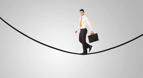 Happy businessman walking on rope. A confident smiling salesman balancing on black wire in clear grey empty space concept Royalty Free Stock Image