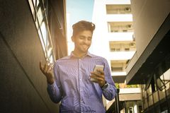 Businessman walking trough street and typing on smart phon stock photo