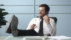 Happy businessman wearing headphones listening to music at workplace. Happy funky businessman relaxing wearing wireless headphones listening to music pretending stock video footage
