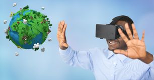 Happy businessman wearing VR glasses while gesturing by low poly earth Stock Photography