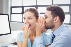 Happy businessman whispering to female colleague. Close-up of happy businessman whispering to female colleague in office Royalty Free Stock Photography