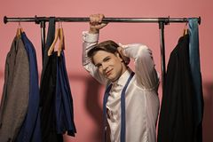 Happy businessman in white shirt, blue necktie on pink background. Man hold rack with jackets on hangers in wardrobe. Clothing, dressing, closet. Business stock images