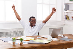 Happy businessman win. Winner, black man in office. Happy excited businessman celebrate. Winner, black man in office with laptop Royalty Free Stock Photos