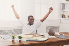 Happy businessman win. Winner, black man in office. Happy excited businessman celebrate. Winner, black man in office with laptop Stock Photography