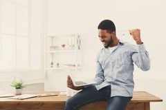 Happy businessman win. Winner, black man in office. Happy excited businessman celebrate his success. Winner, black man in office reading on laptop, copy space Stock Photography