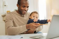 Happy businessman working and babysitting. Working and babysitting. Handsome alert bearded afro-american men smiling and working on the laptop while a child Royalty Free Stock Image