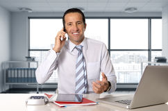 Happy businessman working on computer laptop talking on mobile phone at office Royalty Free Stock Photography