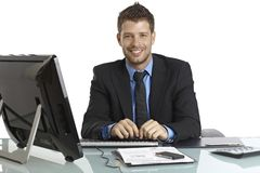 Happy businessman working at desk Royalty Free Stock Photos