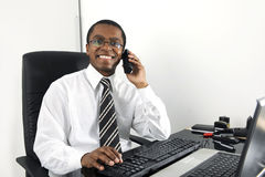 Happy businessman working at desk smiling. On phone Royalty Free Stock Images