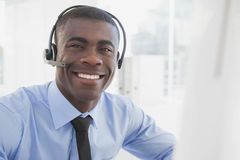 Happy businessman working at his desk wearing headset Royalty Free Stock Photography