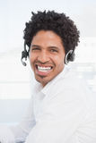 Happy businessman working at his desk wearing headset Royalty Free Stock Photos