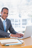 Happy businessman working on his laptop Stock Photography