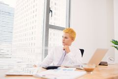 Happy businessman working at his office with laptop. Young smili Stock Photos