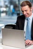 Happy businessman working on laptop Stock Photo