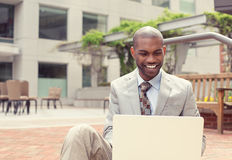 Happy businessman working on laptop computer outdoors. Handsome young happy businessman working on laptop computer outdoors on a background of corporate office Stock Photo